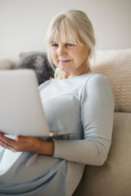 Hermosa mujer madura usando la computadora portátil en la