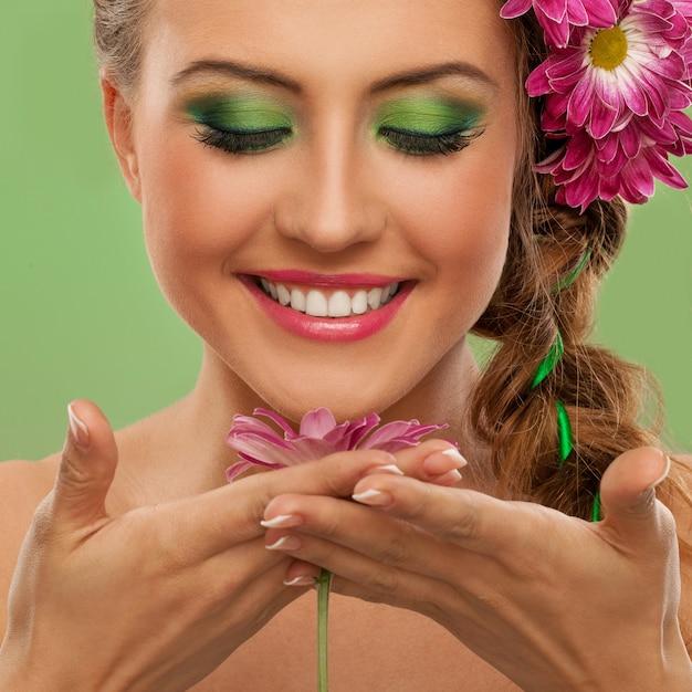 Hermosa mujer con maquillaje y flores. Foto gratis