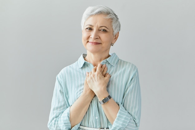 Hermosa mujer de mediana edad de aspecto amistoso con una sonrisa sincera, que expresa gratitud, se siente agradecida, muestra su corazón lleno de amor, manteniendo las manos en el pecho. sentimientos humanos genuinos positivos Foto gratis