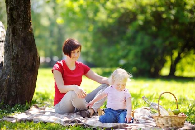 Hermosa mujer de mediana edad y su pequeño nieto adorable que tienen una comida campestre en parque soleado Foto Premium