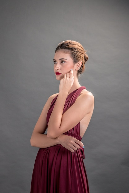 eda1f150a Hermosa mujer modelo posando sobre fondo gris