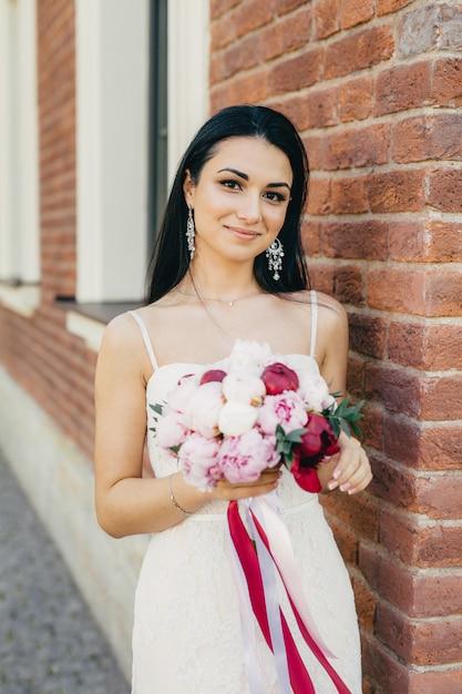 Hermosa mujer morena con apariencia encantadora, usa arete, vestido de novia blanco y tiene un hermoso ramo Foto Premium