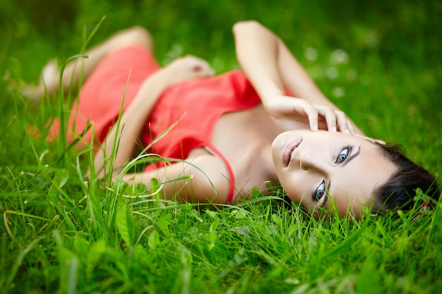 Hermosa mujer morena modelo tumbado en verano verde hierba brillante en el parque con maquillaje en vestido rojo. Foto gratis