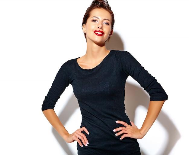 Hermosa mujer morena sexy feliz en vestido negro casual con labios rojos en la pared blanca Foto gratis