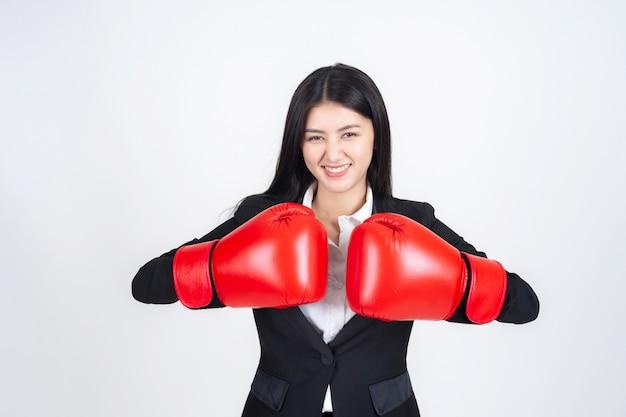 Hermosa mujer de negocios asiática con un guante de boxeo en la mano y traje de negocios Foto gratis