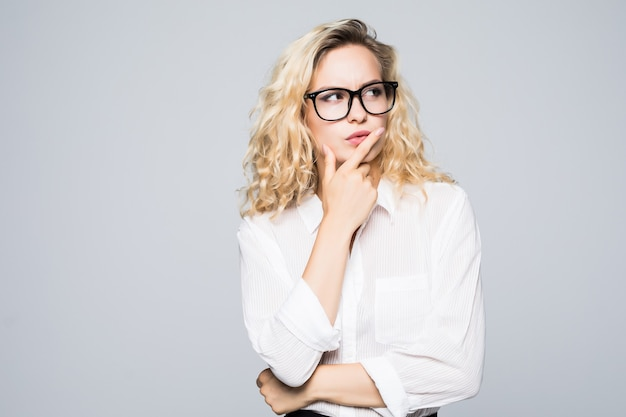 Hermosa mujer de negocios rubia pensamiento aislado pared blanca Foto gratis