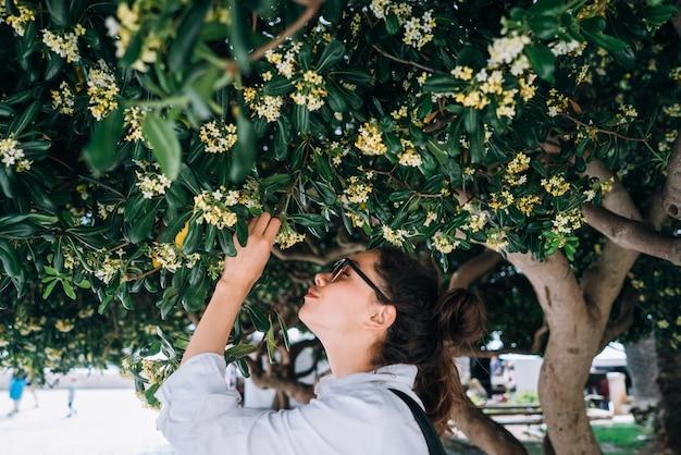 Hermosa mujer oliendo las flores de los árboles. tiempo de primavera Foto gratis