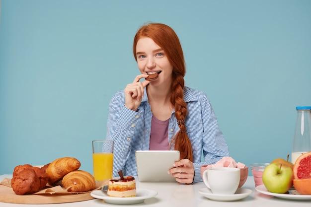 Hermosa mujer pelirroja sonriente desayunando leyendo noticias en su tableta mirando al frente y comiendo galletas de chocolate Foto gratis