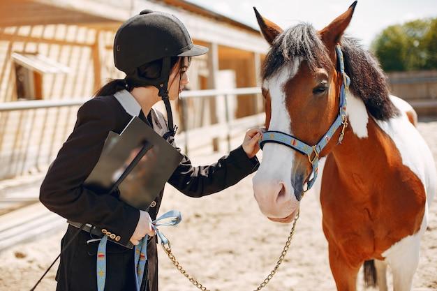 Hermosa mujer de pie con un caballo Foto gratis