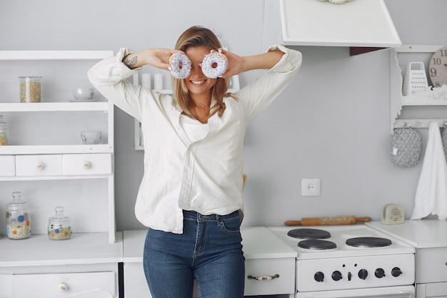 Hermosa mujer de pie en una cocina con donut Foto gratis