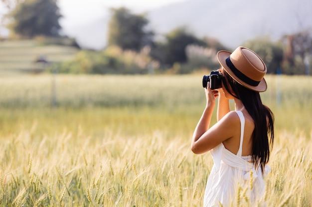 Una hermosa mujer que disfruta disparando en campos de cebada. Foto gratis