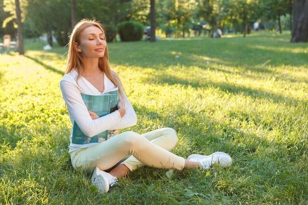 Hermosa mujer respirando aire fresco, sentada en el césped del parque Foto Premium