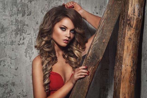 Hermosa mujer rizada en vestido rojo Foto gratis