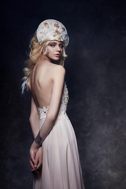 Hermosa mujer rubia vestida con la espalda desnuda y una tiara en la cabeza Foto Premium