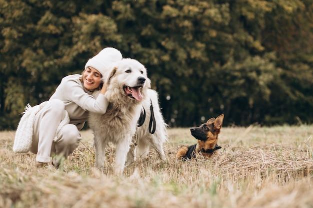 Hermosa mujer saliendo de sus perros en un campo Foto gratis