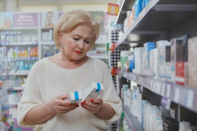Hermosa mujer senior de compras en la farmacia Foto Premium