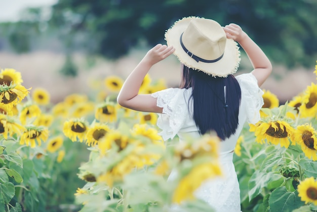 Hermosa mujer sexy con un vestido blanco caminando en un campo de girasoles Foto gratis