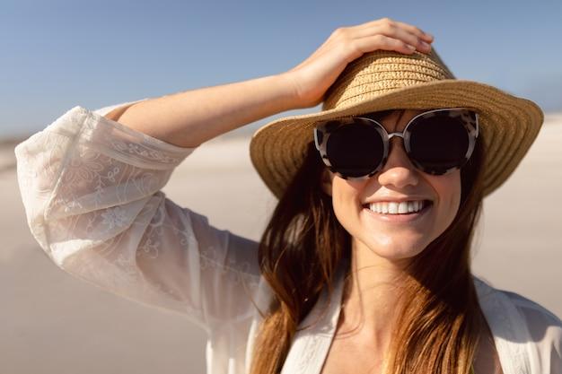 Hermosa mujer con sombrero y gafas de sol de pie en la playa bajo el sol Foto gratis