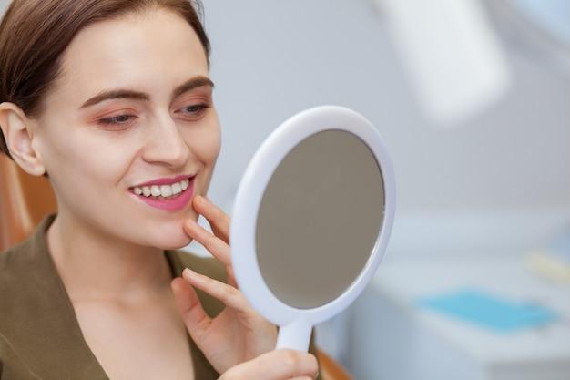 Hermosa mujer sonriendo, mirando en el espejo en la clínica dental Foto Premium