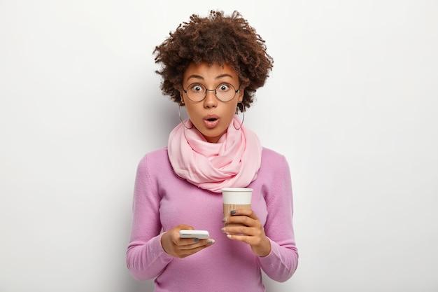 Hermosa mujer sorprendida con cabello nítido revisa las noticias, recibe un mensaje de sorpresa, sostiene café para llevar, no puede creer en algo, usa lentes ópticos y un suéter púrpura, posa en interiores Foto gratis