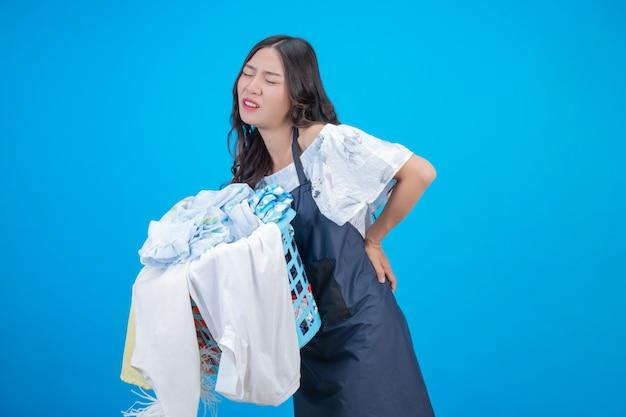 Hermosa mujer sosteniendo una canasta de ropa en azul Foto gratis