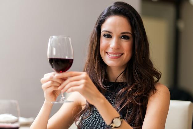 Hermosa mujer sosteniendo una copa de vino tinto Foto Premium