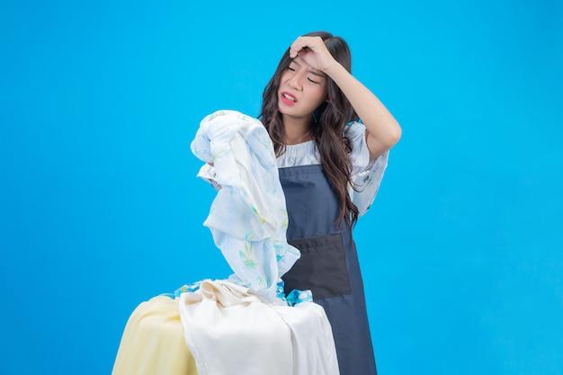 Una hermosa mujer sosteniendo un paño preparado para lavar en azul Foto gratis