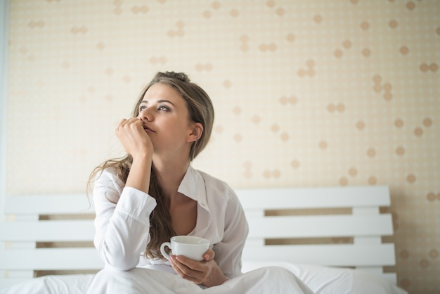Hermosa mujer en su habitación tomando café por la mañana Foto gratis