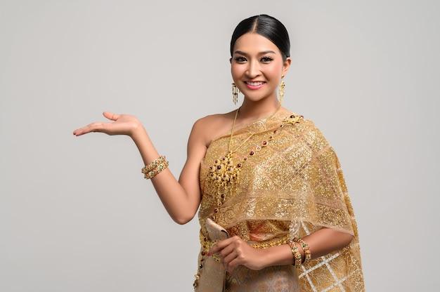 Hermosa mujer tailandesa usa ropa tailandesa y abre su mano a la derecha Foto gratis