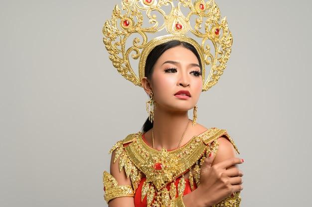 Hermosa mujer tailandesa con vestido tailandés y de pie abrazándose a sí misma Foto gratis