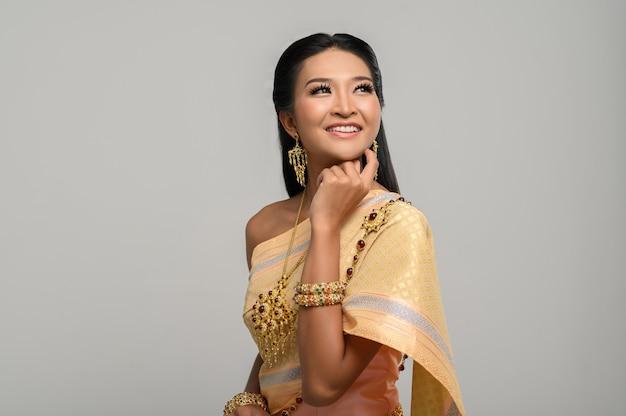 Hermosa mujer tailandesa con un vestido tailandés y una sonrisa feliz. Foto gratis