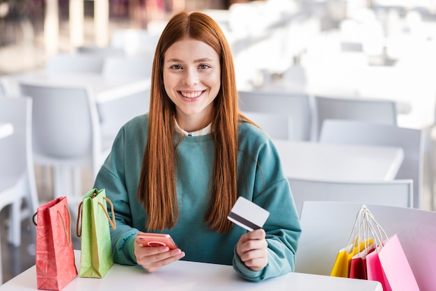 Hermosa mujer con teléfono y tarjeta de crédito Foto gratis