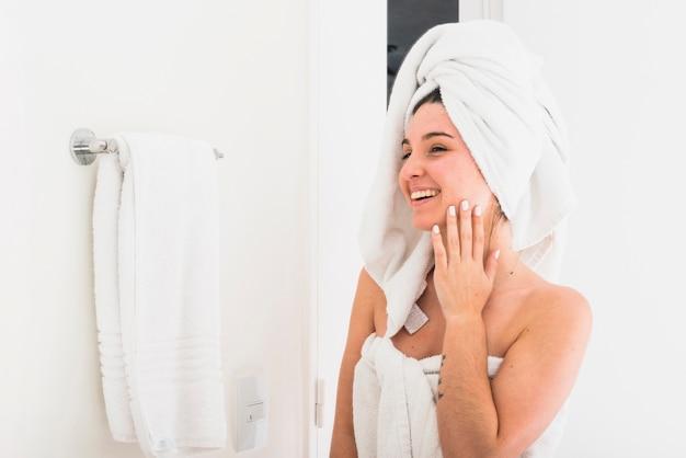 Hermosa mujer con una toalla envuelta en la cabeza mirando en el espejo Foto gratis