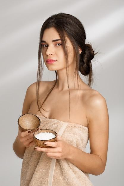 Hermosa mujer en toalla suave con exfoliante de sal antes del masaje. Foto gratis