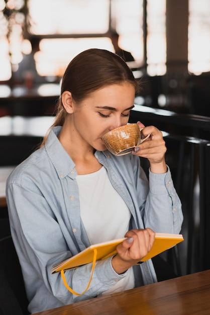 Hermosa mujer tomando café y sosteniendo un cuaderno Foto gratis