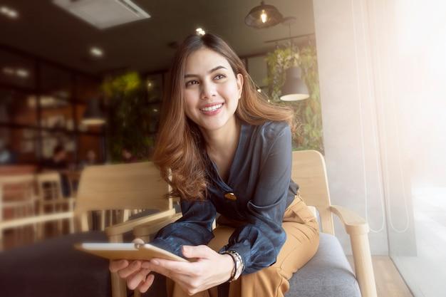 Hermosa mujer está trabajando con tableta en cafetería Foto Premium