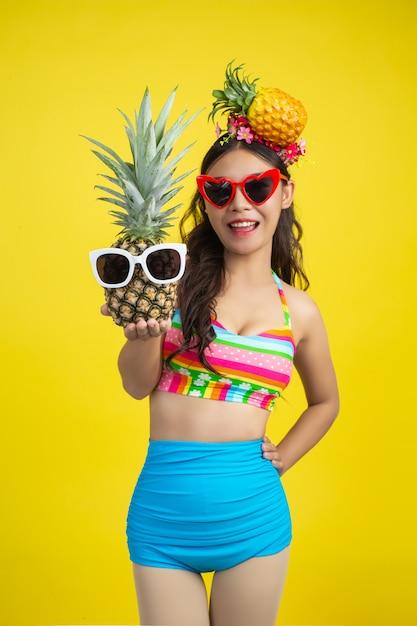 Hermosa mujer en traje de baño sosteniendo una piña posa en amarillo Foto gratis