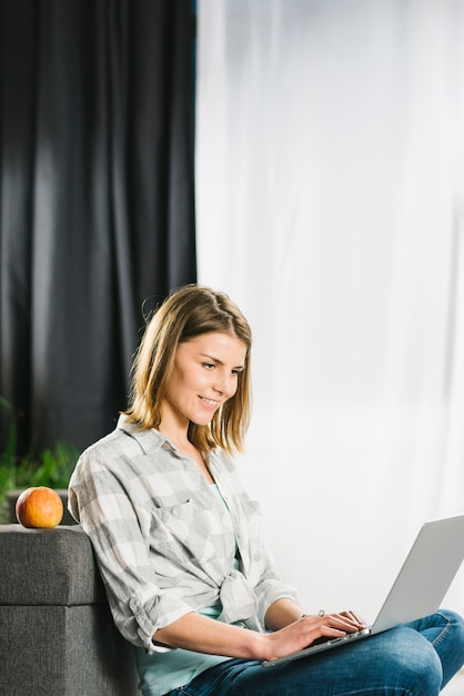 Hermosa mujer usando laptop cerca de sofá Foto gratis