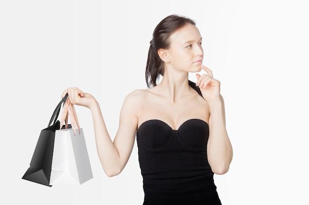 Hermosa mujer vestida de negro con bolsas de compras