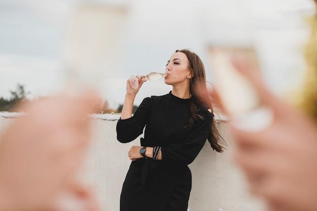 Hermosa mujer en vestido negro bebiendo champán en el fondo de copas de champán borrosas Foto gratis