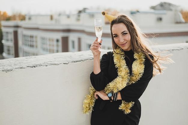 Hermosa mujer en vestido negro con una copa de champán Foto gratis