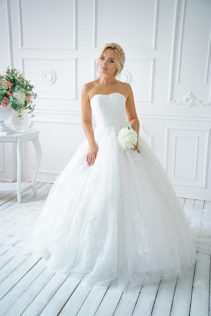 Hermosa mujer en un vestido de novia con un hermoso maquillaje y cabello Foto Premium