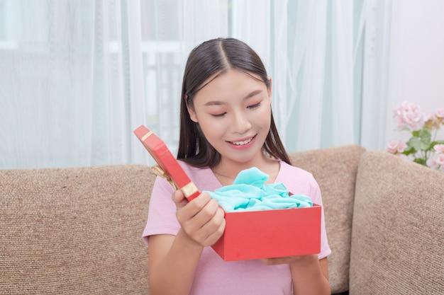 Hermosa mujer en vestido rosa, sentada en el sofá, abriendo una caja de regalo. Foto gratis