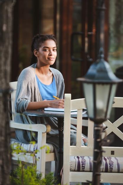 Hermosa niña africana escribiendo en el cuaderno Foto gratis