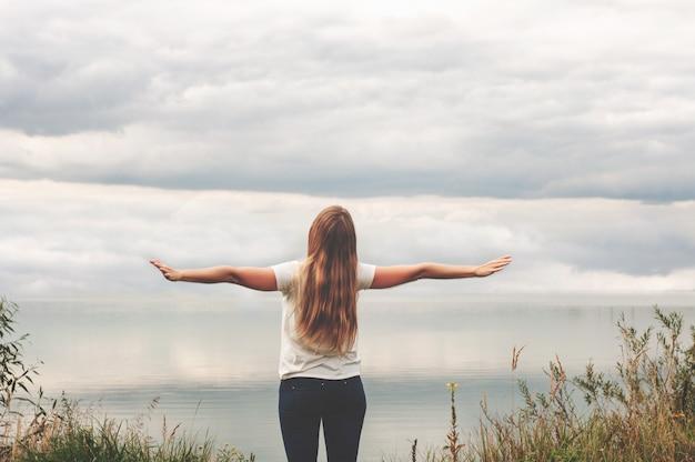 Una hermosa niña se encuentra en la orilla, vista posterior. manos arriba. puesta de sol. clases de yoga. Foto Premium