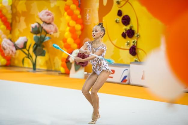 Hermosa niña gimnasta activa con su actuación en la alfombra Foto Premium