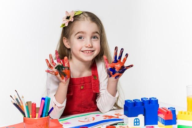 La hermosa niña con las manos en la pintura Foto gratis