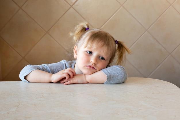 Hermosa niña niño triste o aburrido se sienta junto a la mesa Foto Premium