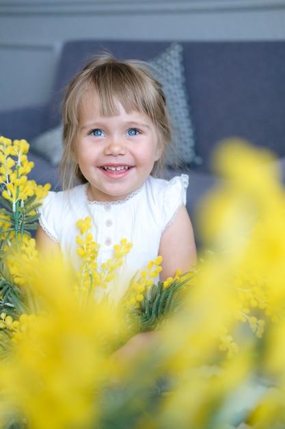 Una hermosa niña de ojos azules y ligeras trenzas sonríe. en primer plano las flores amarillas de mimosa. Foto Premium
