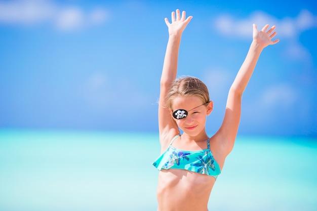 Hermosa niña en la playa divirtiéndose. niña feliz disfrutar del fondo de vacaciones de verano el cielo azul y el agua turquesa en el mar en la isla caribeña Foto Premium